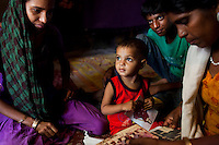 Sadma Khan (left, in purple), 19, rests with her 18 month old toddler (center), at home with her immediate family in her mother's one-room house in a slum area of Tonk, Rajasthan, India, on 19th June 2012. She was married at 17 years old to Waseem Khan, also underaged at the time of their wedding. The couple have an 18 month old baby and Sadma is now 3 months pregnant with her 2nd child and plans to use contraceptives after this pregnancy. She lives with her mother since Waseem works in another district and she can't take care of her children on her own. Photo by Suzanne Lee for Save The Children UK