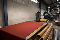 Fabbrica di tessuti, tessuto rosso steso su un tavolo e operaio sullo sfondo Bute tartan mills
