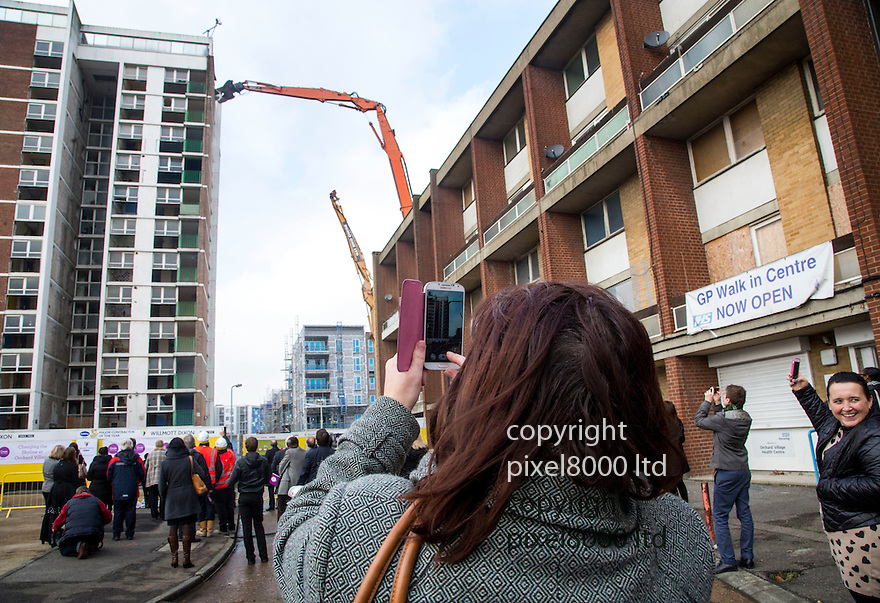 Pic shows: Roman House, Mardyke Estate, Dagenham East London - Demolition of last of famous tower blocks as used in Made In Dagenham film and Fish Tank.<br /> <br /> Residents came out in force to see <br /> <br /> originally used to house Ford Motor Company workers.<br /> <br /> An &pound;80m regeneration project which is transforming an infamous London housing estate into a thriving community today reached a major milestone when the demolition of the last remaining tower block got underway. <br />  <br /> Residents came together to celebrate as a monster muncher started to bring down the final 12 storey tower block, marking a historic moment for the Rainham estate, which achieved notoriety in recent years having appeared in the films Made in Dagenham and Fish Tank.<br />  <br /> Orchard Village &ndash; previously known as the Mardyke Estate&ndash; was a 1960s high rise estate that over time became dilapidated and a haunt for anti social behaviour. The estate&rsquo;s reputation for crime meant that no one on the housing list of over 4,000 wanted to live there, resulting in flats remaining empty. <br /> <br /> <br /> <br /> <br /> Pic by Gavin Rodgers/Pixel 8000 Ltd