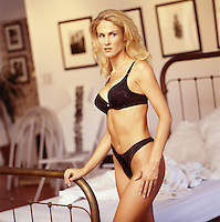 Photo of a beautiful Blond Woman standing near an antique brass bed. She's wearing Black Lingerie.