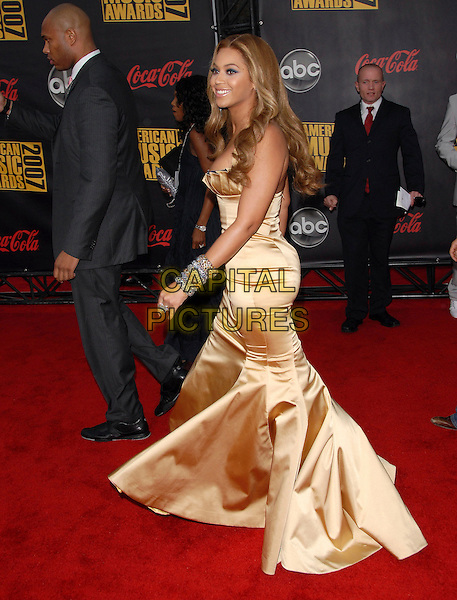BEYONCE KNOWLES.At The 35th Annual American Music Awards held at The Nokia Theatre in Los Angeles, California, USA, .November 18, 2006..full length gold yellow satin strapless dress  grey silver bracelets  .CAP/DVS.©Debbie VanStory/Capital Pictures