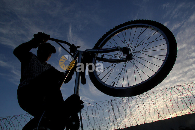 A Palestinian youth displays acrobatic skills on his bicycle during the weekly sport event, in the al-Zahra town, southern Gaza city, on Jan. 19, 2013. Photo by Ezz al-Zanoon