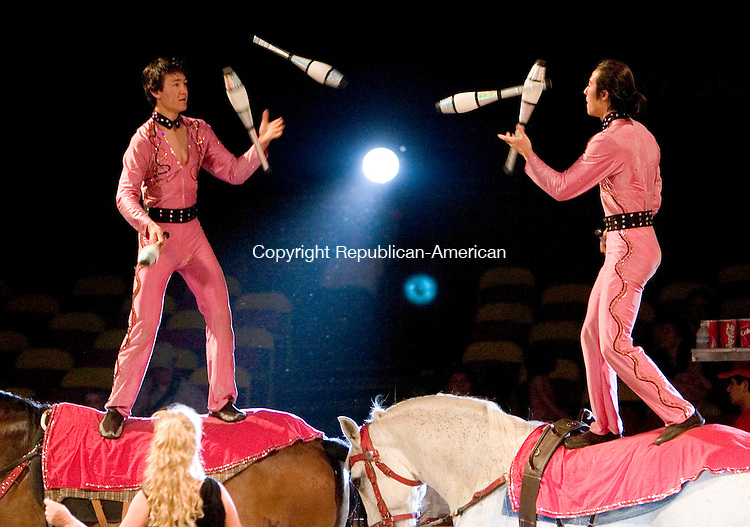 MIDDLEBURY, CT- 12 JUNE 2007- 061207JT10-<br /> <br /> Brothers Victor and Vladimir Kim juggle back and forth while standing on trotting horses while their mother Luba guides the horses in the foreground during a show at the Cole Bros. Circus at Middlebury Technology Center on Tuesday afternoon. The Middlebury Volunteer Fire Department hosted the circus to raise money for the department and other community events they sponsor.<br /> Josalee Thrift Republican-American