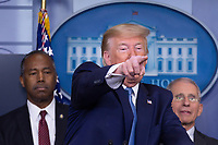 United States President Donald J. Trump, joined by members of the Coronavirus Task Force, gestures as makes remarks on the Coronavirus crisis in the Brady Press Briefing Room of the White House in Washington, DC on Saturday, March 21, 2020. At left is United States Secretary of Housing and Urban Development (HUD) Ben Carson; and at right is Director of the National Institute of Allergy and Infectious Diseases at the National Institutes of Health Dr. Anthony Fauci.  Credit: Stefani Reynolds / Pool via CNP/AdMedia