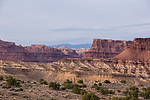Layered sandstone formations  make up the rugged San Rafael Reef on the eastern edge of the San Rafael Swell in south central Utah.  In the distance are the Book Cliffs.