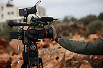A member of the Israeli military puts his hand on the lens of a camera as he tries to prevent coverage, as others investigate the attack on the Hamayel home, that was burnt by suspected Jewish extremists using petrol bombs, in the village of Abu Falah, northeast of Ramallah, on November 23, 2014. Suspected Jewish extremists firebombed a house in a Palestinian village in the occupied West Bank early, its mayor told AFP, pointing the finger of blame at local settlers. Masud Abu Mura, mayor of Khirbet Abu Falah, said four women were inside the house at the time, but they all escaped unharmed. Photo by Shadi Hatem