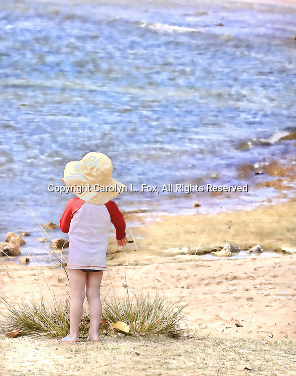 A little girl stands in the sand by the ocean.