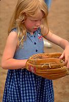 Girl age 5 looking at baseball glove. Dunning Field St Paul  Minnesota USA