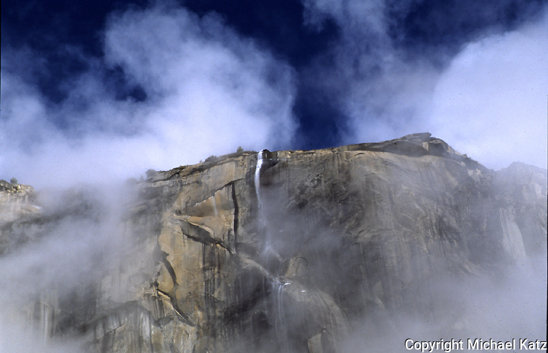 Cascade breaking through fog near El Capitan.