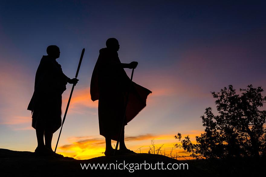 Masaai warriors on a kopje at sunset. Ngorongoro Conservation Area / Serengeti National Park, Tanzania.