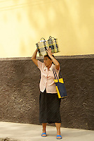 Indigenous woman carrying a basket on her head in the Spanish colonial town of Gracias, Lempira, Honduras...