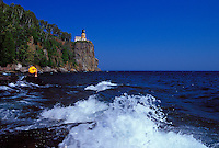 A BOY EXPLORES THE ROCKY SHORE BELOW THE SPLIT ROCK LIGHTHOUSE  AT SPLIT ROCK LIGHTHOUSE STATE PARK NEAR TWO HARBORS, MINNESOTA.