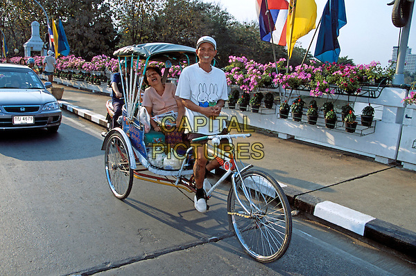 Bicycle rickshaw driver and passenger sitting in rickshaw, Chiang Mai, Northern Thailand