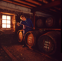 Scotland. Malt whisky bond store. Distillery worker checking content of barrel stored whisky.  Whisky is traditionally stored in oak sherry casks..