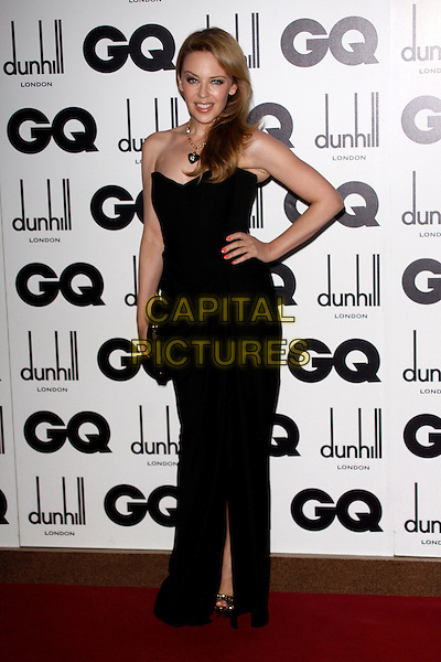Kylie Minogue.GQ Men Of The Year Awards - arrivals, The Royal Opera House, London, England..September 4th, 2012.full length dress hand on hip clutch bag black strapless gold chain silver heart necklace .CAP/AH.©Adam Houghton/Capital Pictures.