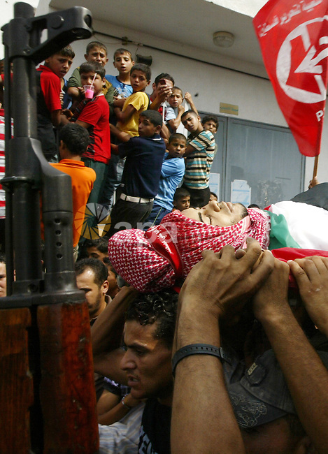 Palestinian relatives carry the body of  Qassim al-Shinbari, a militant from the Popular Front for the Liberation of Palestine (PFLP), during his funeral in the town of Beit Hanoun in northern Gaza Strip July 22, 2010. Israeli shellfire killed two Palestinian militants, one of them al-Shinbari, and wounded six people, including a 10-year-old girl, in the Gaza Strip on Wednesday, Palestinian medical workers and an official with a militant group said. An Israeli military spokeswoman said soldiers opened fire on militants suspected of preparing to fire a rocket at them. A security source said the troops fired a tank shell. Photo by Ashraf Amra