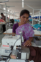 An indian woman using a sophisticated Yamata machine  at Srinidhi garment stitching factory in Tirupur, Tamilnadu. After lifting of quota system in textile export on 1st january 2005. Tirupur has become the biggest foreign currency earning town of India.