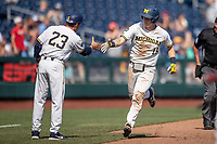 Michigan Wolverines first baseman Jimmy Kerr is greeted by third base coach Nick Schnable (23) after his second home run of the game against the Texas Tech Red Raiders in the NCAA College World Series on June 21, 2019 at TD Ameritrade Park in Omaha, Nebraska. Michigan defeated Texas Tech 15-3 and will play in the CWS Finals. (Andrew Woolley/Four Seam Images)