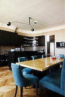 In the kitchen/dining room the curved cabinets have been made from grained oak stained a deep chocolate brown and the work surfaces are of coffee-coloured stone