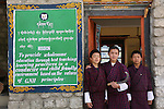 "Notice about ""Gross National Happiness teaching practice"" at Wangdue Chhoeling Lower Secondary School, Bumthang, Bhutan..Bhutan the country that prides itself on the development of 'Gross National Happiness' rather than GNP. This attitude pervades education, government, proclamations by royalty and politicians alike, and in the daily life of Bhutanese people. Strong adherence and respect for a royal family and Buddhism, mean the people generally follow what they are told and taught. There are of course contradictions between the modern and tradional world more often seen in urban rather than rural contexts. Phallic images of huge penises adorn the traditional homes, surrounded by animal spirits; Gross National Penis. Slow development, and fending off the modern world, television only introduced ten years ago, the lack of intrusive tourism, as tourists need to pay a daily minimum entry of $250, ecotourism for the rich, leaves a relatively unworldly populace, but with very high literacy, good health service and payments to peasants to not kill wild animals, or misuse forest, enables sustainable development and protects the country's natural heritage. Whilst various hydro-electric schemes, cash crops including apples, pull in import revenue, and Bhutan is helped with aid from the international community. Its population is only a meagre 700,000. Indian and Nepalese workers carry out the menial road and construction work."