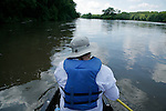 Back view of a man in the front of a canoe paddling on the Fox River near Yorkville, Illinois.
