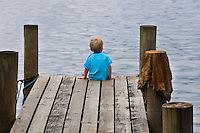 A two year old boy sitting on the end of the dock, Bocas del Toro, Colon Island, Panama