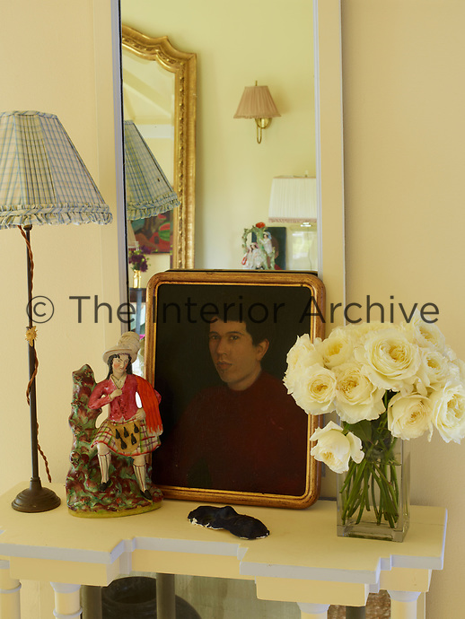 A collection of items is arranged on a white side table comprising a portrait, a flower arrangement in a glass vase, a figurine and a slender table lamp. A mirror hangs behind the table.