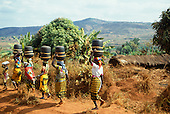 Tanzania. Line of women carrying identical black baskets on their heads.