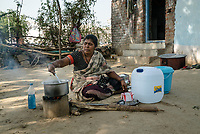 Rani barukaum, the SHG group leader cooks lunch in the courtyard of her house in Ambedkar Nagar in Medak, Telangana, India.