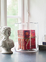 Vintage books with bright red covers displayed in a glass vase and a bust from Slottstallet are displayed on the kitchen window sill