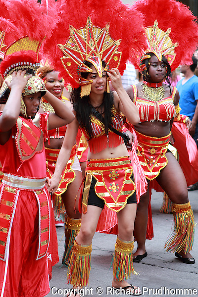 young woman in their flamboyant costumes take part in the Carifiesta parade in downtown Montreal