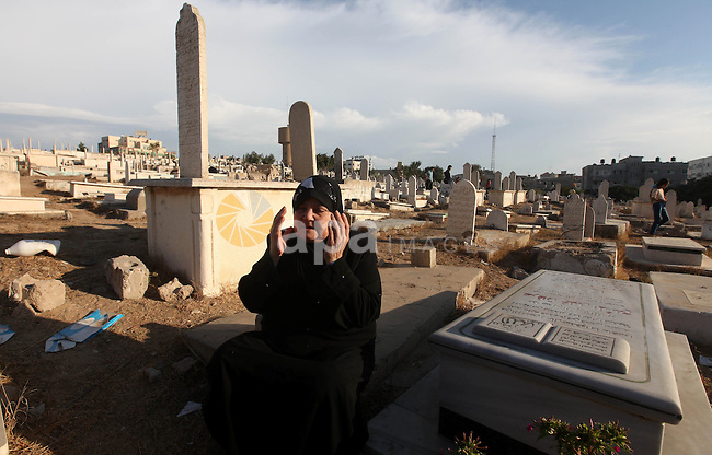 Palestinians visit the graves of relatives at a cemetery in Gaza city on the first day of Eid al-Adha, on October 26, 2012 as Muslims worldwide commemorate Eid al-Adha, or the Feast of the Sacrifice, marking the end of the hajj and commemorating Abraham's willingness to sacrifice his son Ismail on God's command. Photo by Majdi Fathi