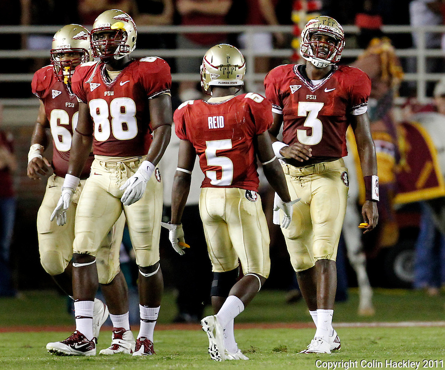 TALLAHASSEE, FL 9/17/11-FSU-OU091711 CH-Florida State's EJ Manuel, right, walks off the field after throwing an interception against Oklahoma during first half action Saturday at Doak Campbell Stadium in Tallahassee. .COLIN HACKLEY PHOTO