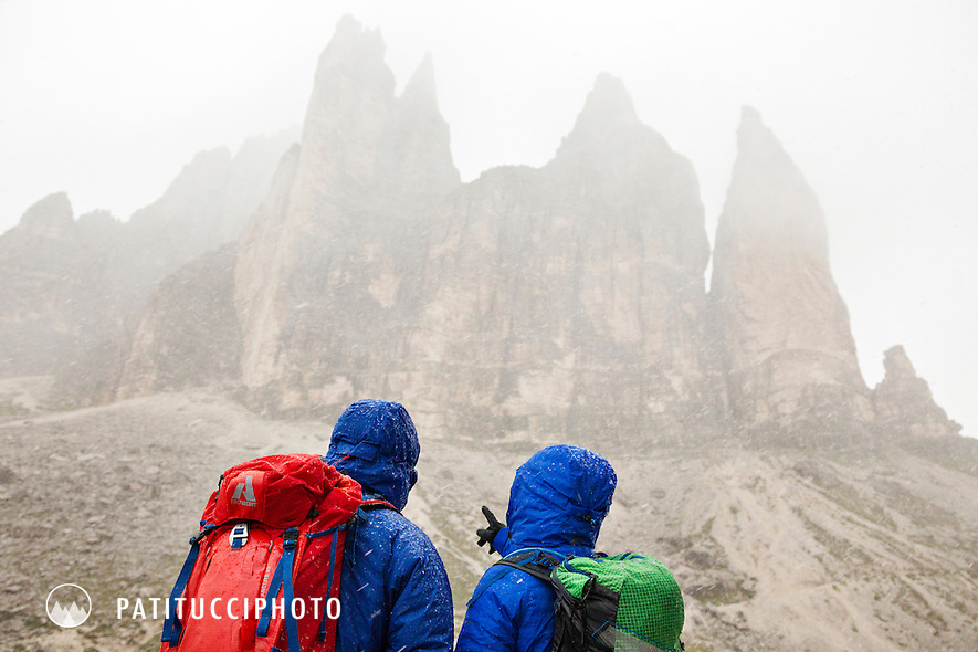 Two hikers in heavy rain beneath the Tre Cime di Lavaredo