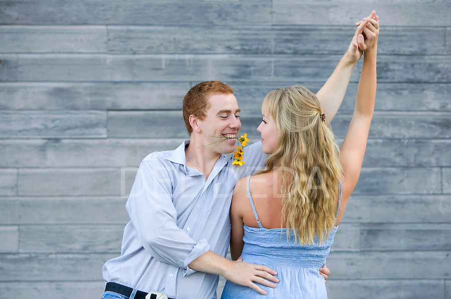 An attractive young couple dances together outside.