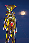 The man and full moon at the Burning man arts and counter culture festival in the Black Rock desert near Gerlach, NV, 2009