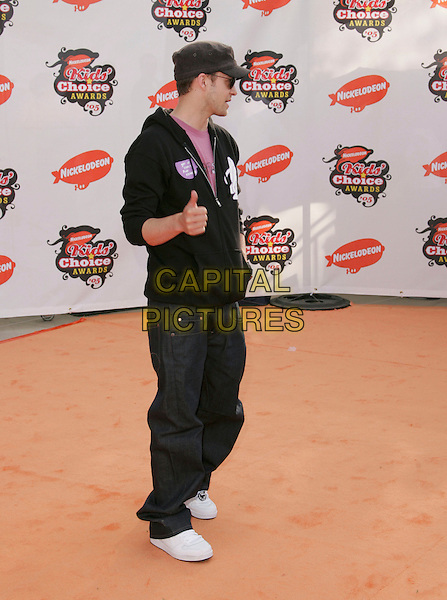 JUSTIN TIMBERLAKE.Attends Nickelodeon's 18th Annual Kids' Choice Awards Show held at UCLA's Pauley Pavilion in Westwood, California, April 2nd 2005..full length hat cap shades sunglasses glases watch hoodie hooded top pink t-shirt t shirt hands in pockets thumbs up gesture.Ref: DVS.www.capitalpictures.com.sales@capitalpictures.com.©Debbie VanStory/Capital Pictures