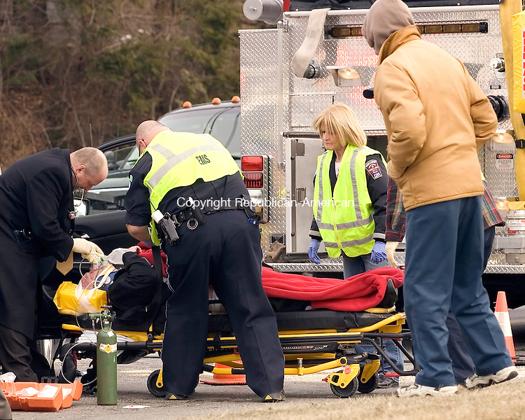 Middlebury, CT-05, February 2010-020510CM08  Emergency medical personnel render first aid to one of the occupants following a two car collision which occurred Friday afternoon on Middlebury Rd (Rt 64) in Middlebury.  The collision occurred in front of TD Bank, forcing traffic to be rerouted through the banks parking lot.  Three people from the collision were transported to the hospital.  The injuries appeared to be non life threatening, stated  Lt. Wildman of the Middlebury Police Department.  --Christopher Massa Republican-American