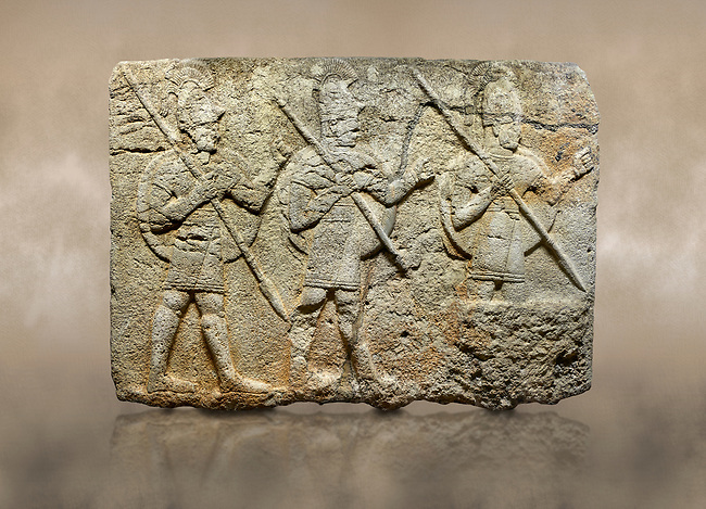 Photo of Hittite monumental relief sculpted orthostat stone panel from the Herald's Wall. Basalt, Karkamıs, (Kargamıs), Carchemish (Karkemish), 900-700 B.C. Military parade. Anatolian Civilisations Museum, Ankara, Turkey. Two helmeted soldiers in short skirts carry the shield on their backs and the spears in their hands.  <br /> <br /> Against a brown art background.