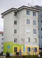 A gentleman stands outside an apartment block with World Cup graffiti painted on in Sao Paulo, one of the 12 host cities of the 2014 FIFA World Cup