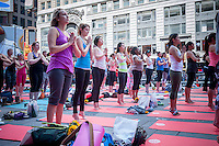 "Thousands of yoga practitioners pack Times Square in New York to practice yoga on the first day of summer, Sunday, June 21, 2015. The 13th annual Solstice in Times Square, ""Mind Over Madness"",  this year takes place on the United Nations' International Day of Yoga. Times Square stretches the yogis' ability to block out the noise and the visual clutter that surround them in the Crossroads of the World. (© Richard B. Levine)"