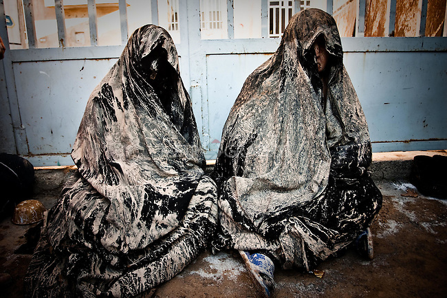 """KHORRAMABAD, IRAN : Two women with mud drying on their """"chador""""--traditional clothes...Every year to mark the death of Imam Hussein, Shia Muslims mourn for two days. In Khorramabad and Lorestan in the west of Iran, during the first day of mourning, called Tasooa, women take a vow of silence and go through the streets with the children lighting candles. At 4 am on Ashura, the second day, men cover themselves in mud and then stand in front of a fire until the mud has dried to clay. After this they go to the mosque and pray...Photo by Farhad Babaei/Metrography"""