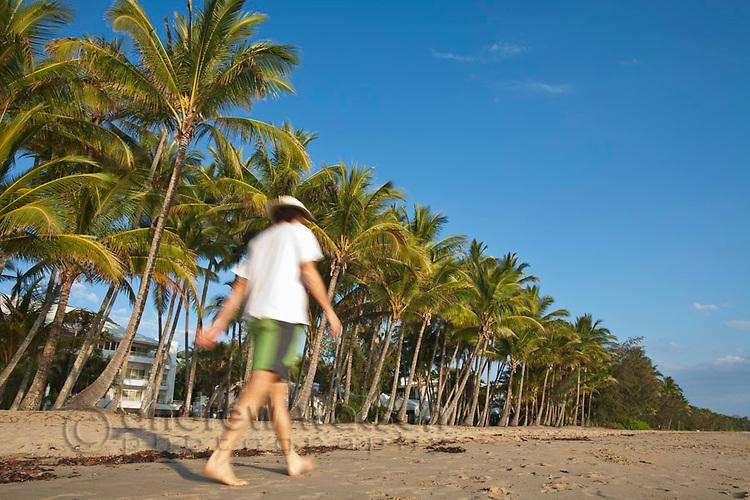 Man walking along beach.  Palm Cove, Cairns, Queensland, Australia