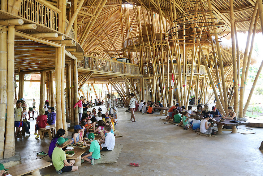 """Students meeting for lunch in the Heart of School for a great selection of organic food<br /><br />The Green School (Bali) is one of a kind in Indonesia. It is a private, kindergarten to secondary International school located along the Ayung River near Ubud, Bali, Indonesia. The school buildings are of ecologically-sustainable design made primarily of bamboo, also using local grass and mud walls. There are over 600 students coming from over 40 countries with a percentage of scholarships for local Indonesian students.<br /><br />The impressive three-domed """"Heart of School Building"""" is 60 metres long and uses 2500 bamboo poles. The school also utilizes renewable building materials for some of its other needs, and almost everything, even the desks, chairs, some of the clothes and football goal posts are made of bamboo.<br /><br />The educational focus is on ecological sustainability. Subjects taught include English, mathematics and science, including ecology, the environment and sustainability, as well as the creative arts, global perspectives and environmental management. This educational establishment is unlike other international schools in Indonesia. <br /><br />Renewable energy sources, including solar power and hydroelectric vortex, provide over 50% of the energy needs of the school. The school has an organic permaculture system and prepares students to become stewards of the environment. <br /><br />The school was founded by John and Cynthia Hardy in 2008."""