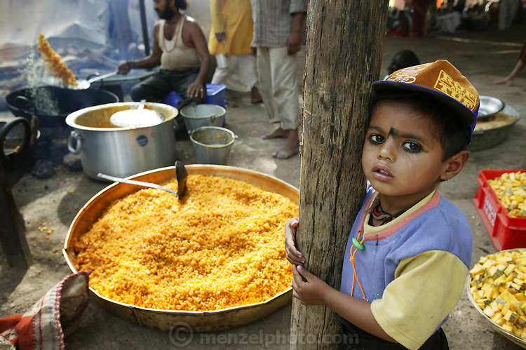 Sweet, fried boondi, a spiced chickpea flour confection, is prepared for pilgrims in a camp at an ashram during the Kumbh Mela festival in Ujjain, Madhya Pradesh, India. (From the book What I Eat: Around the World in 80 Diets.) Every camp has its own large/small kitchen where food is prepared for people residing in that particular camp as well as outsiders who would walk in and out for lunch/dinner. Boondi can be a savory preparation or even sweet. A thin consistency dough is prepared using gram flour, water and spices. This boondi can be made sweet by putting in sugar syrup (prepared separately) and soaked in the syrup. Cardamom, dry fruits may be added in the syrup for flavor. The Kumbh Mela festival is a sacred Hindu pilgrimage held 4 times every 12 years, cycling between the cities of Allahabad, Nasik, Ujjain and Haridwar.  Participants of the Mela gather to cleanse themselves spiritually by bathing in the waters of India's sacred rivers.  Kumbh Mela is one of the largest religious festivals on earth, attracting millions from all over India and the world.  Past Melas have attracted up to 70 million visitors.