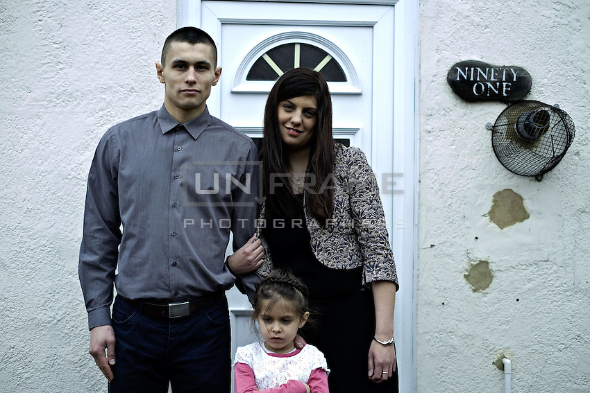 Przemek Kierpacz, his wife and his daughter pose in front of their home. London, UK, 9th March 2015.