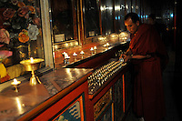 Monk fills butter lamps in Xia Qiong Temple, Qinghai, China. Qinghai Province in western China borders Tibet and parts were the scenes of disturbance earlier this year, 2008..12 Nov 2008