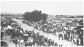 A large crowd of people and horse-drawn vehicles line a street in Santa Clara Pueblo, perhaps for a race.<br /> Santa Clara Pueblo, NM  Taken by Pepper, George - 1903