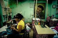 Cuban women work in front of a large portrait of the revolutionary leader Che Guevara, hung on the wall of dress-maker's in Havana, Cuba, 13 February 2009. During the Cuban Revolution, an armed rebellion at the end of the 1950s in Cuba, most of the revolutionary leaders started as no-name soldiers fighting in the jungle. Although the revolutionary leaders, after taking over the power, became autocratic rulers holding almost absolute power and putting the opposition in jail, for some reason Cuban people have never stopped to worship Fidel Castro, Che Guevara, Raul Castro and others. Cubans hang their photos and portraits on the wall in homes, shops and working places even they don't have to. The people of Cuba love their heroes.