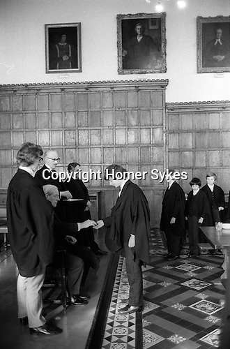 Kings Scholars line up and collect their annual traditional 3d piece from the College Provost. Known as Threepenny Day. Eton near Windsor Berkshire, England 1975.<br /> <br /> Kings Scholars or Collegers as they are known line up to receive a new threepenny piece from the Provost in a 400 years old tradition.<br /> <br /> Dr Roger Lupton 1456&ndash;27 February 1539 or 1540 was an English ecclesiastic, lawyer-cleric, chaplain to Henry VII and also to Henry VIII and Provost of Eton from 1502-1535.( The chairman of Eton&rsquo;s governing body. )   His death is commemorated each year on 27 February at Eton College. <br /> <br /> The annual distribution took place after lunch in the College Hall by the Provost Harold Caccia,(Provost 1965-1977) and was confined to the seventy Kings Scholars. Originally the Provost received 2s 8d, other members of staff 1s 4d and less depending on status. Scholars and choristers received 1d each. The scholars still received the one penny in a three penny pieces, the other twopence being from the gift of Provost Bost who succeeded Lupton.<br /> <br /> With the introduction of decimal coinage in 1972, and the abolition of the threepenny piece. Provost Caccia bought up large stocks of redundant coin to ensure continuation of this custom.<br /> <br /> The Captain of School, Provost Harold Caccia, The College Butler with tray and  Master-in-College, Rev. Canon P. Pilkington.<br /> <br /> The Captain of the School would get any 3ds left over owing to absentees.